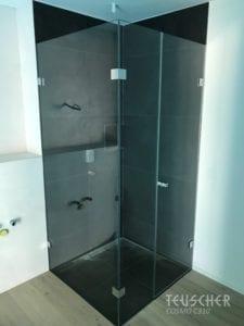 Ebenerdige Dusche mit schwarzem Hintergrund.