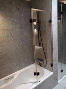 Ein klappbarer Badewannenaufsatz eignet sich perfekt als Duschwand.