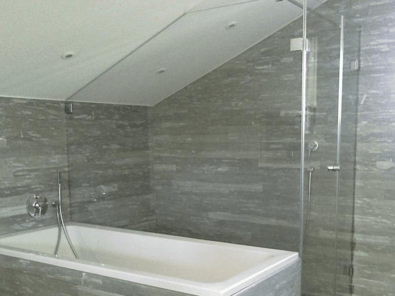 Dusche unter Dachschräge neben Steinbadewanne.