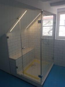 Dusche unter Dachschräge mit Sitzbank auf der Seite der Schräge.