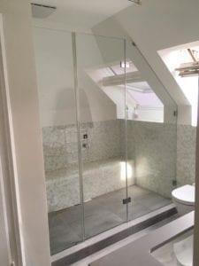 Dusche unter Dachschräge mit Fenster in der Schräge.