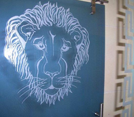 Eine Glasdusche mit Motiv: Löwenkopf.