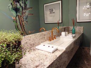 Bad mit Marmorwaschtisch und grünen Wänden.