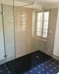 Dusche mit weissen Metro-Plättli an der Wand und schwarzen Boden-Plättli.