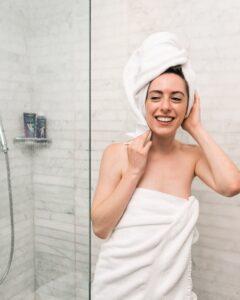Gesund duschen: Frau kommt erfrischt aus der Dusche.
