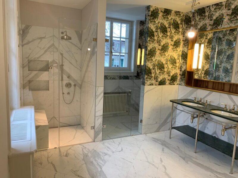 Vintage-Badezimmer im Jugendstil mit Marmor und Blumentapete.